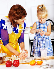 Grandmother and grandchild baking cookies.