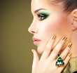 Glamour woman with beautiful golden nails and emerald ring