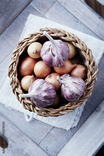 Onions and garlic bulbs in a rustic basket