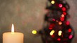Burning candle with christmas tree in background