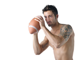 Handsome shirtless young man holding american football ball