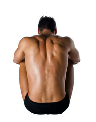 Muscular back of shirtless young man sitting on the floor