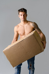 Athletic, shirtless young man carrying big cardboard box