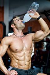 Muscular male bodybuilder drinking water or energy drink