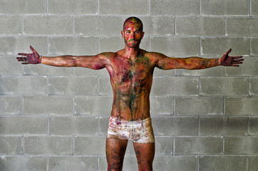 Attractive young man with skin painted with Holi colors