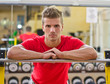 Attractive young man in gym resting on barbell