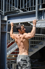 Muscular male bodybuilder seen from back, hanging from structure