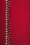 Gold chain and rhinestones lying on red fabric poster