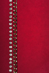 Gold chain and rhinestones lying on red fabric
