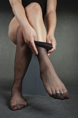 Woman legs putting on black hold-ups