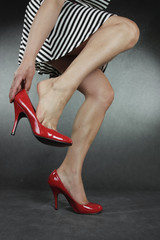 Woman putting on high heel shoes over grey background