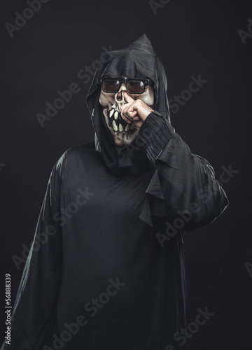 skeleton in a robe picks his nose