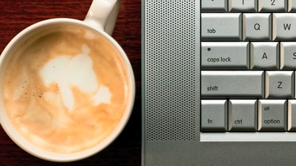Close up of a cappuccino coffee and laptop computer