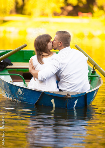 Handsome man hugging girlfriend on boat