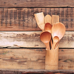 Kitchen wooden utensils in retro bucket over wooden background