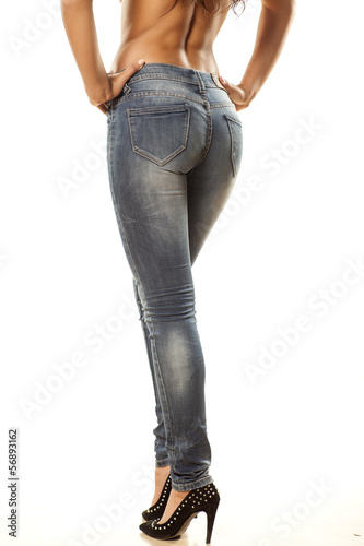 view from behind on the pretty female legs in jeans on  white
