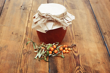 sea buckthorn berries juice on the glass jar on wooden table