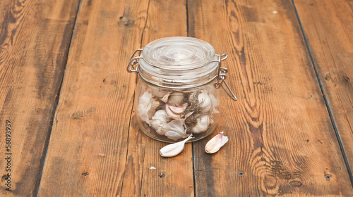 fresh garlic in glass jar  on old wooden table