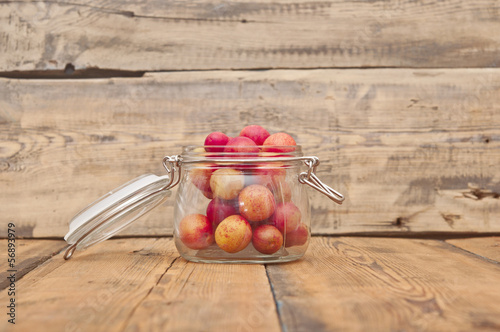 freshly picked plum in glass jar on old wooden table