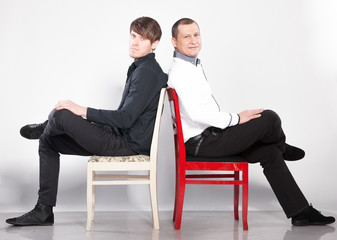 Two men sitting on chairs back to back