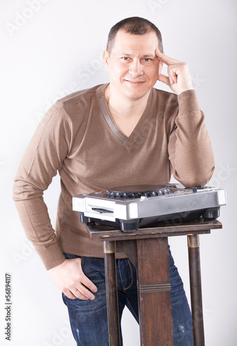 Handsome man posing near DJ control panel