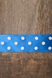 Wooden background with blue polka-dot ribbon