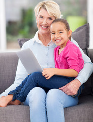 little girl sitting on grandmother's lap with notebook computer