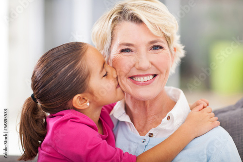 cute granddaughter kissing her grandmother