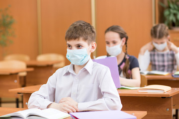 pupils with protection mask against flu virus at lesson