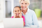 senior woman and her grandchild in front of laptop