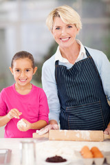 little girl and granny baking at home