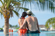 happy young couple relax and take fresh drink on poolside