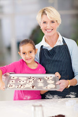 grandmother and granddaughter holding tray of cookies to be bake
