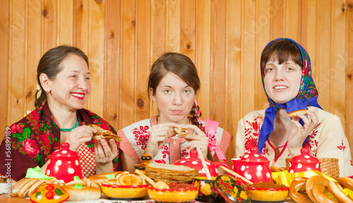 Women eating pancake   during  Pancake Week