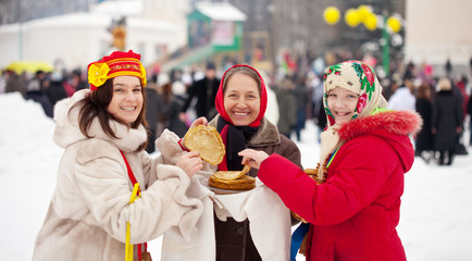 Women eating pancakes during  Maslenitsa