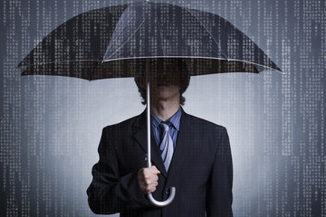 Businessman with an umbrella under digital rain.