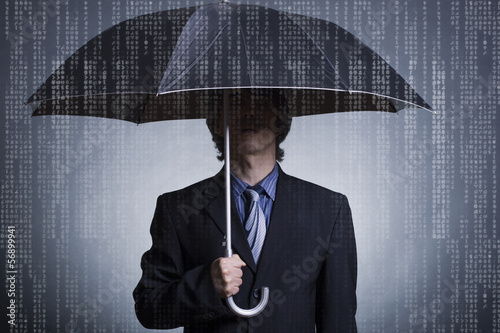 Businessman with an umbrella under digital rain.