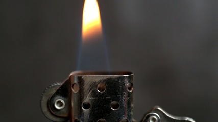 Cigarette lighter with flame. Selective focus.