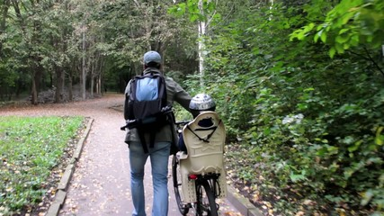 A father and son walking in the park on a bike
