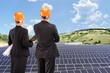 Team of architects examining solar panels under sunny sky