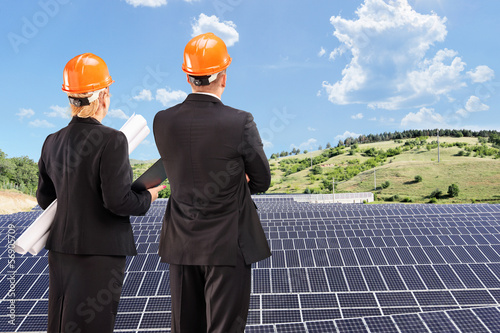 Team of architects examining solar panels under sunny sky