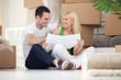 couple sitting on floor looking at house plans