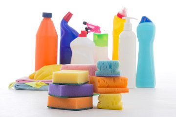 Plastic bottles of cleaning products and sponges isolated on whi