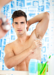 man applying antiperspirant