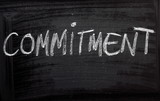 The word Commitment on a Blackboard poster
