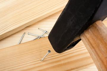 Nagel in Holz einschlagen