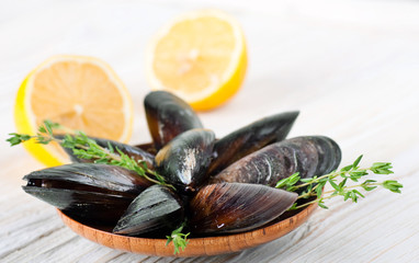Mussels in the shell with lemon on wooden background