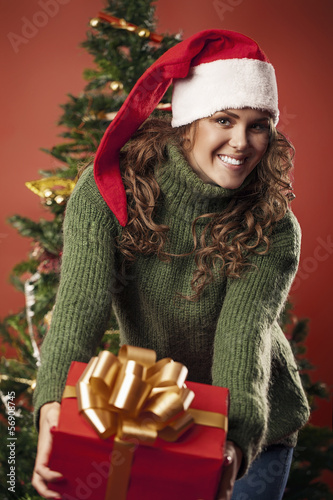 Beautiful girl is showing a Christmas gift
