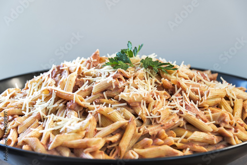 Large bowl full of Penne A La Vodka topped with parmesan cheese
