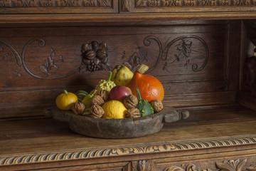 Eine Holzschale mit Herbstfüchen auf einem Antiken Schrank.